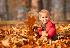 Child Playing In Autumn Leaves
