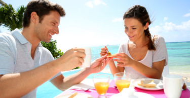 Couple Eating Breakfast On Beach