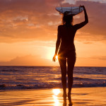 Woman with surfboard at sunset