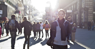 woman walking urban street scene in sunlight